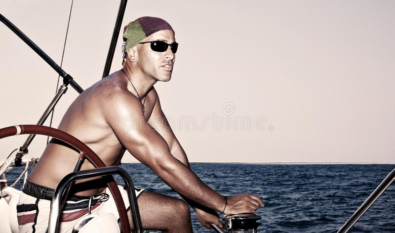 Homem considerável no barco de vela fotografia de stock