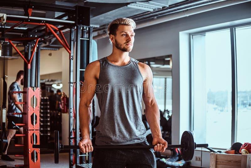 Homem considerável no sportswear que faz o exercício com um barbell no clube ou no gym de aptidão imagem de stock