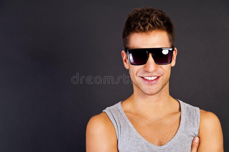 Homem considerável no tanktop cinzento com sorriso e óculos de sol fotos de stock royalty free