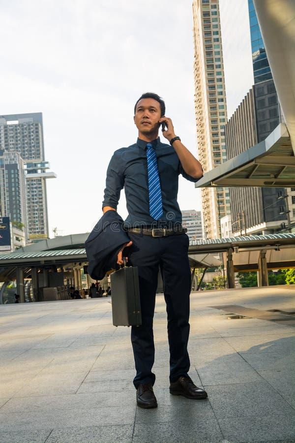 Homem considerável no telefone esperto - homem de negócio novo na cidade moderna foto de stock
