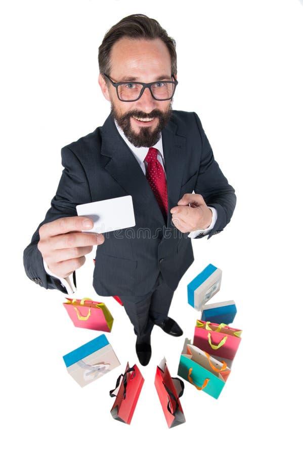 Homem considerável no terno escuro que sorri e que mostra seu cartão do desconto foto de stock