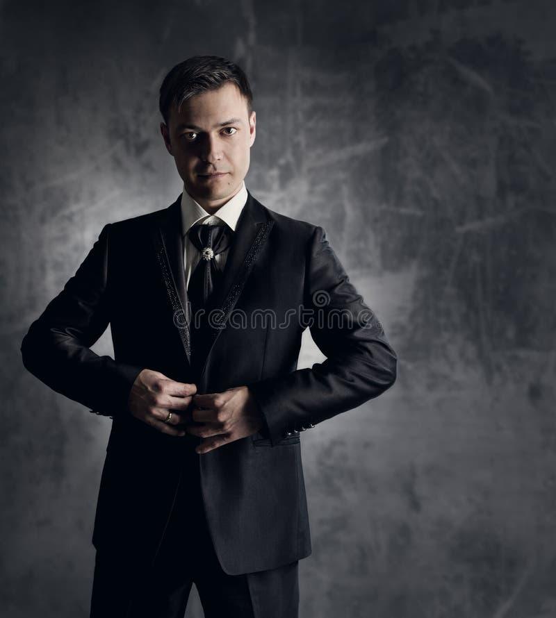 Homem considerável no terno preto. Forma Wedding do noivo. Backgrou cinzento fotos de stock
