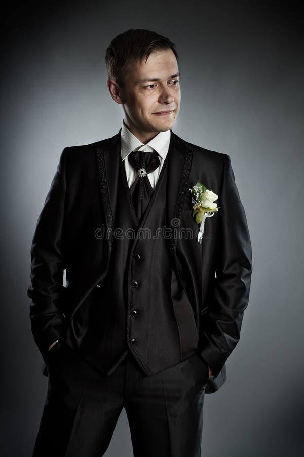 Homem considerável no terno preto. Fundo cinzento. fotografia de stock royalty free