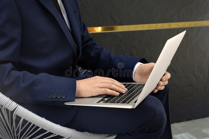 Homem considerável no terno que senta-se com seu portátil fotografia de stock