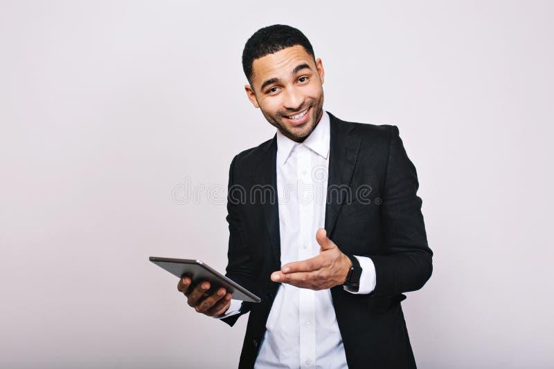 Homem considerável novo à moda na camisa branca, revestimento preto, com tabuleta sorrindo à câmera no fundo branco consiga foto de stock