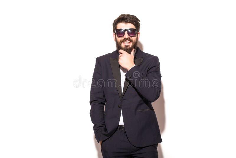 Homem considerável novo alegre nos óculos de sol que mantêm a mão no queixo fotografia de stock