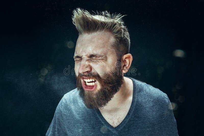 Homem considerável novo com barba que espirra, retrato do estúdio imagem de stock