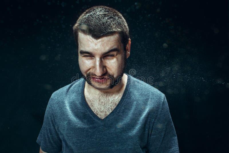 Homem considerável novo com barba que espirra, retrato do estúdio imagem de stock royalty free