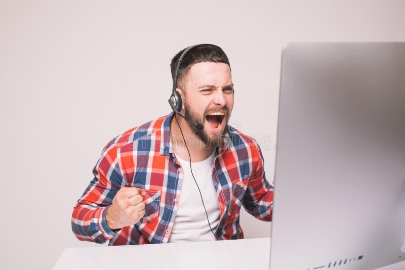 Homem considerável novo com emoções de vencimento felizes da vitória ou de boas notícias na frente do monitor do PC na mesa de es fotografia de stock royalty free