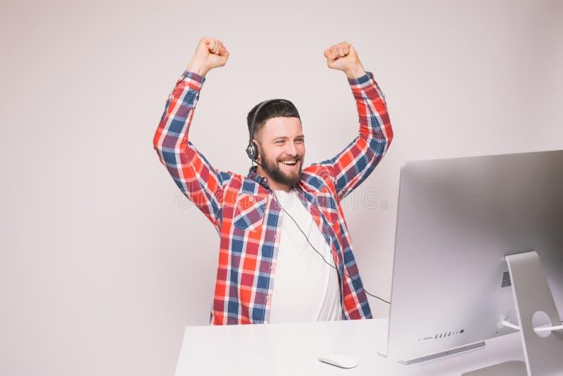 Homem considerável novo com emoções de vencimento felizes da vitória ou de boas notícias na frente do monitor do PC na mesa de es imagem de stock royalty free