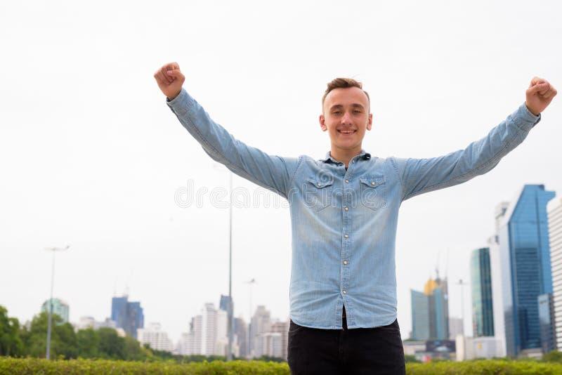 Homem considerável novo com os braços aumentados fora foto de stock royalty free