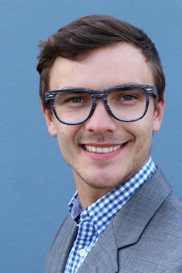 Homem considerável novo com os monóculos vestindo da forma do grande sorriso contra o fundo azul neutro imagens de stock royalty free
