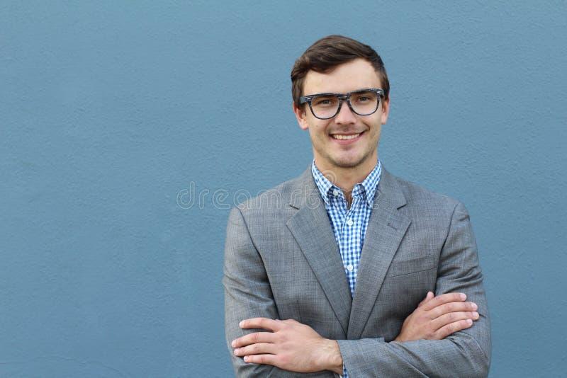 Homem considerável novo com os monóculos vestindo da forma do grande sorriso contra o fundo azul neutro com lotes do espaço da có imagens de stock royalty free