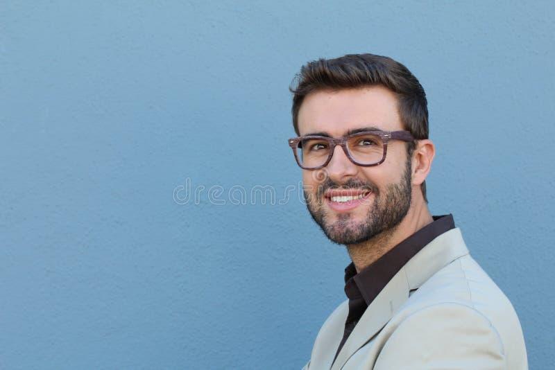 Homem considerável novo com os monóculos vestindo da forma do grande sorriso contra o fundo neutro com lotes do espaço da cópia foto de stock