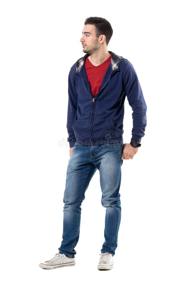 Homem considerável novo de sorriso fresco na camiseta com mãos em uns bolsos traseiros que olham afastado imagem de stock royalty free