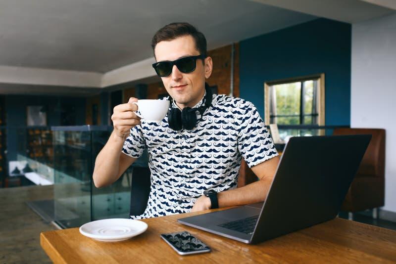 Homem considerável novo do moderno nos óculos de sol que sentam-se no café, guardando a xícara de café Portátil e telefone celula fotografia de stock royalty free