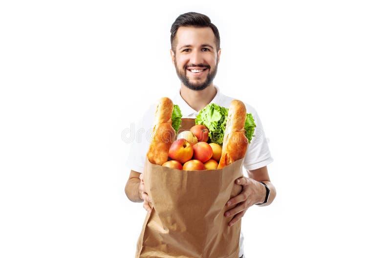 Homem considerável novo do moderno que mantém um saco do alimento isolado em um fundo branco imagem de stock