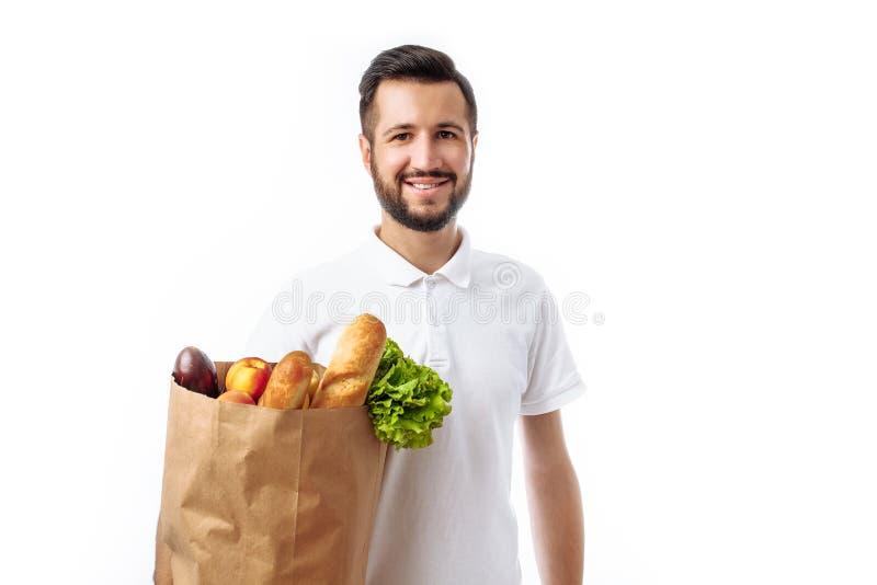 Homem considerável novo do moderno que mantém um saco do alimento isolado em um w imagens de stock royalty free