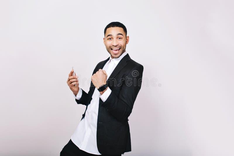 Homem considerável novo do retrato na camisa branca, revestimento preto que tem o divertimento, sorrindo à câmera no fundo branco fotos de stock