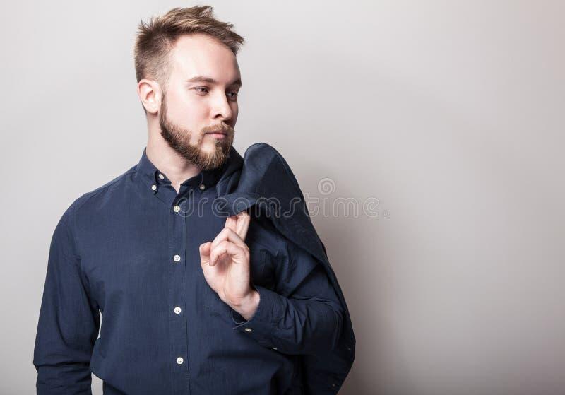 Homem considerável novo elegante na obscuridade - camisa e revestimento clássicos azuis em seu ombro Retrato da forma do estúdio fotografia de stock