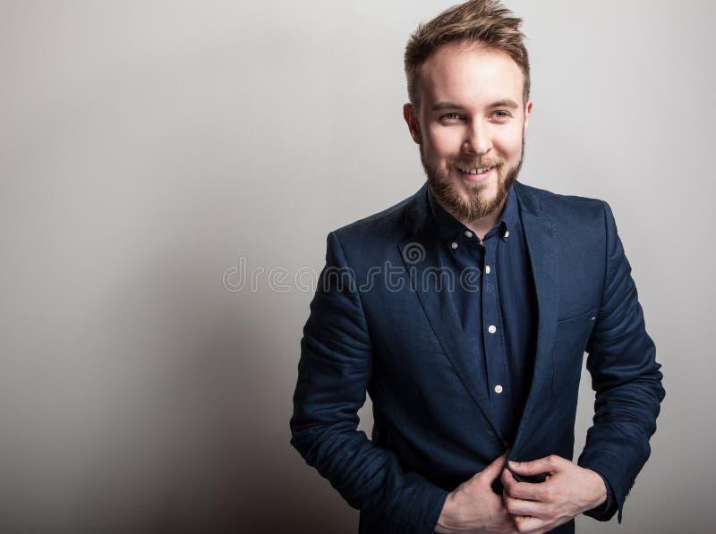 Homem considerável novo elegante na obscuridade clássica - traje azul Retrato da forma do estúdio foto de stock