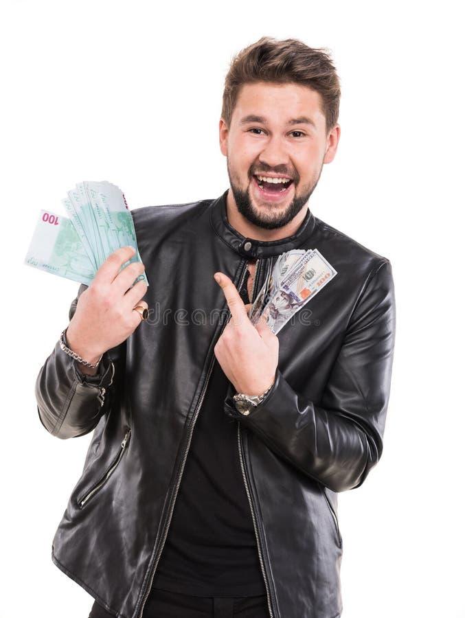 Homem considerável novo em contas pretas do dólar e do euro da terra arrendada do casaco de cabedal fotografia de stock royalty free