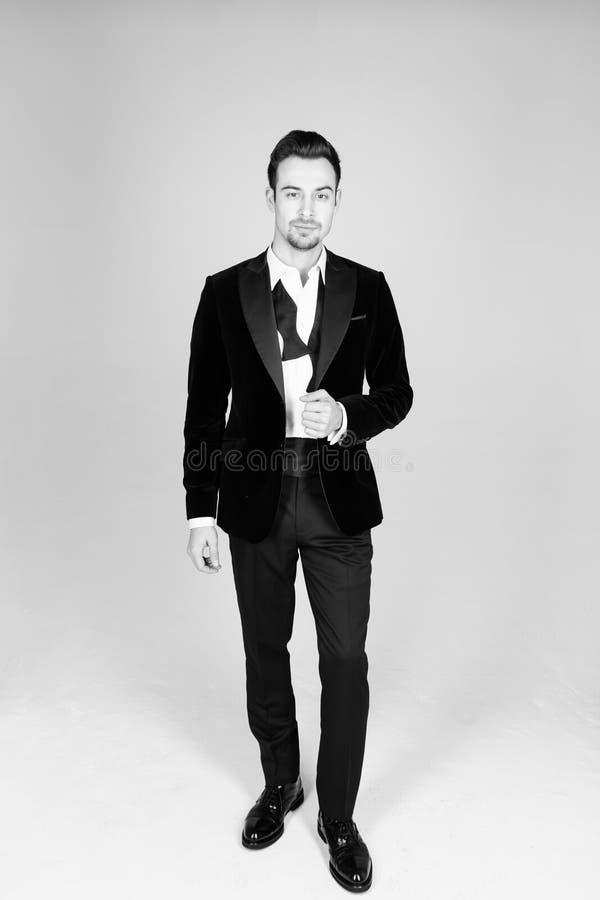 Homem considerável novo em um terno, na posição e em olhar a câmera fotografia de stock
