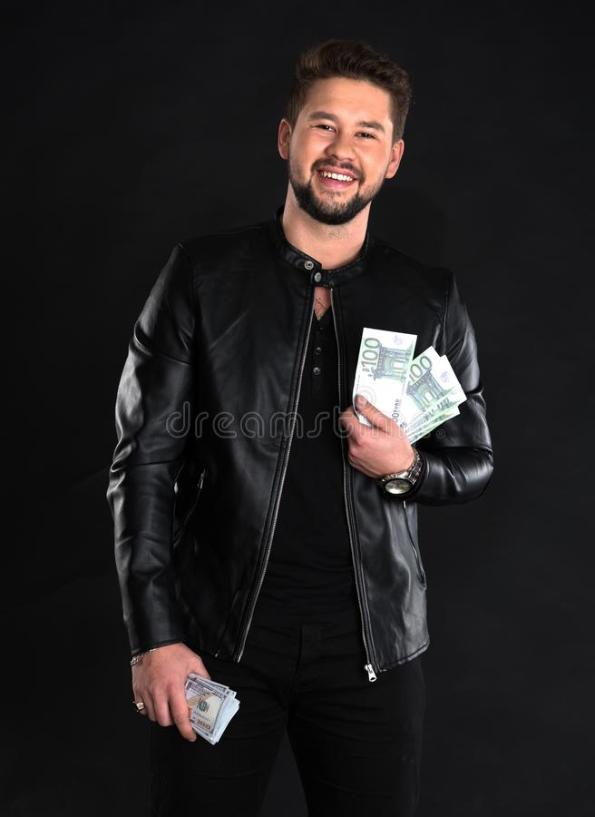 Homem considerável novo no casaco de cabedal preto que guarda notas de dólar fotos de stock royalty free