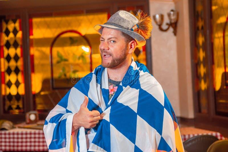 Homem considerável novo no chapéu e com a barba sob o polegar mostrando o mais oktoberfest da bandeira acima foto de stock