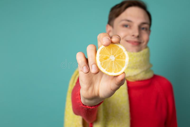 Homem considerável novo no lenço amarelo que mostra o limão cortado do citrino na câmera fotografia de stock royalty free