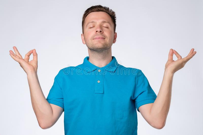 Homem considerável novo no t-shirt azul que relaxa e que sorri com os olhos fechados fazendo o gesto da meditação fotografia de stock