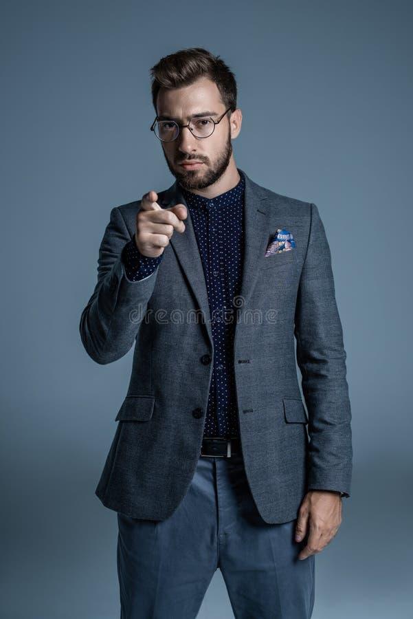 Homem considerável novo no terno formal e vidros que apontam o dedo ilustração do vetor