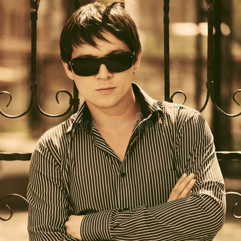 Homem considerável novo nos óculos de sol e em camisa listrada fotos de stock royalty free