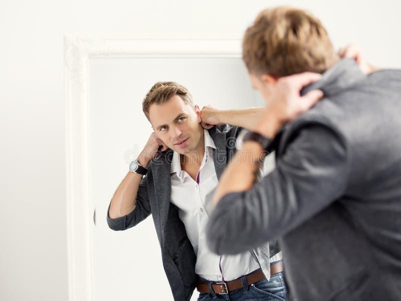 Homem considerável novo ocasionalmente vestido na frente do espelho imagem de stock royalty free