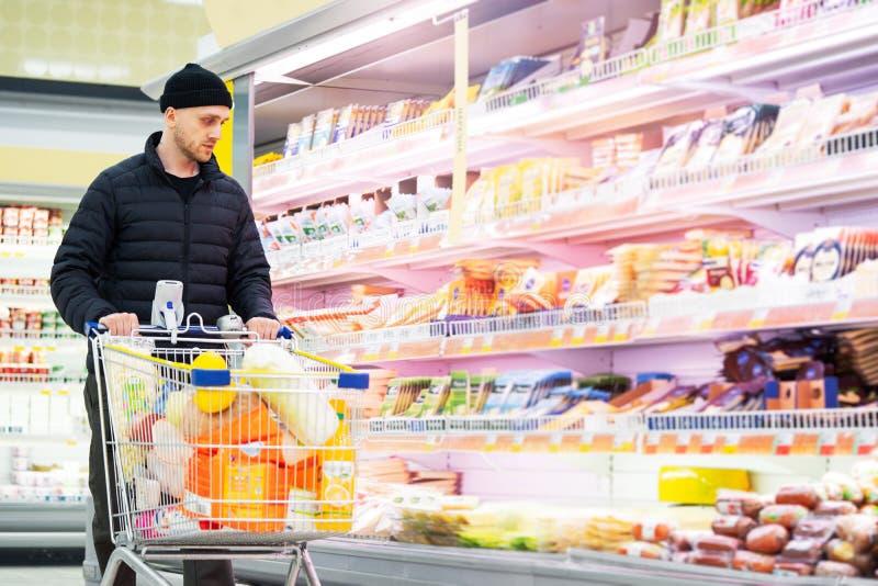 Homem considerável novo que escolhe produtos no supermercado Mat?ria de escolha fotos de stock