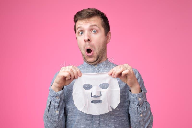 Homem considerável novo que guarda a máscara cosmética e que olha a posição confundida no fundo cor-de-rosa fotografia de stock