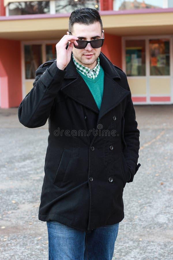 Homem considerável novo que levanta em um revestimento preto do inverno que veste Sunglas foto de stock royalty free