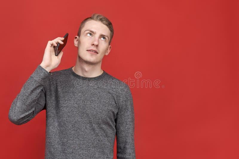 Homem considerável novo que olha acima de conversação aborrecida irritante no telefone homem de negócios cansado de chamadas long foto de stock royalty free