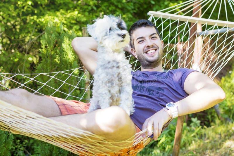 Homem considerável novo que relaxa na rede com seu cão branco imagem de stock