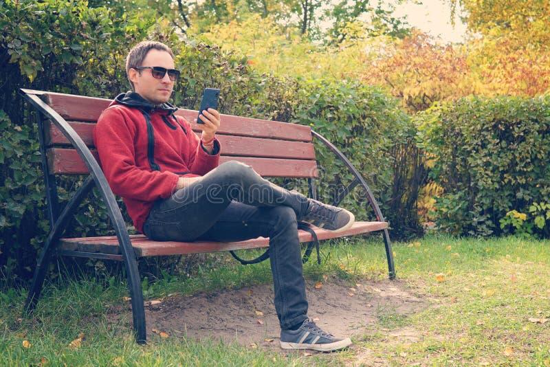 Homem considerável novo que senta-se em um banco que olha sua tela do smartphone O indivíduo lê a mensagem no telefone fotos de stock