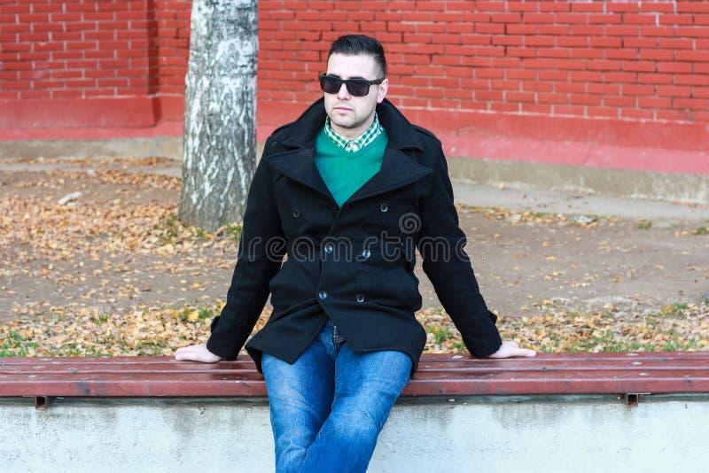 Homem considerável novo que senta-se no banco em vestir preto do revestimento foto de stock