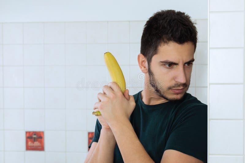 Homem considerável novo que tem o divertimento em sua cozinha imagens de stock royalty free