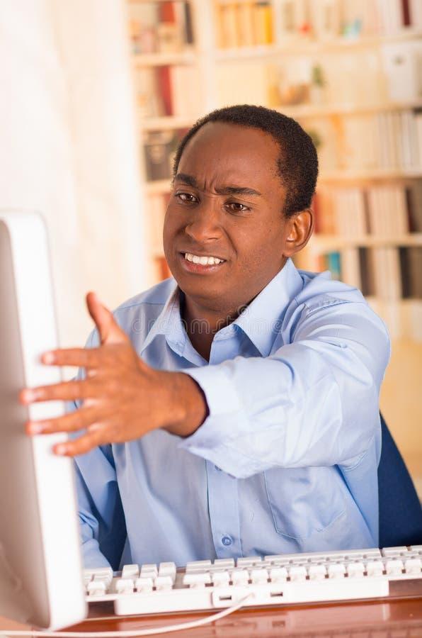 Homem considerável novo que veste a camisa azul do escritório que senta-se pelo computador que faz gestos de mão virados e que ol foto de stock