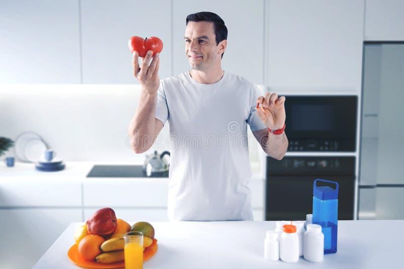 Homem considerável que conduz um estilo de vida saudável e que escolhe as melhores vitaminas fotos de stock royalty free