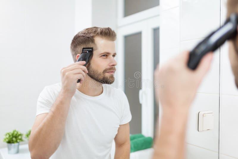 Homem considerável que corta seu próprio cabelo com uma tosquiadeira fotografia de stock royalty free