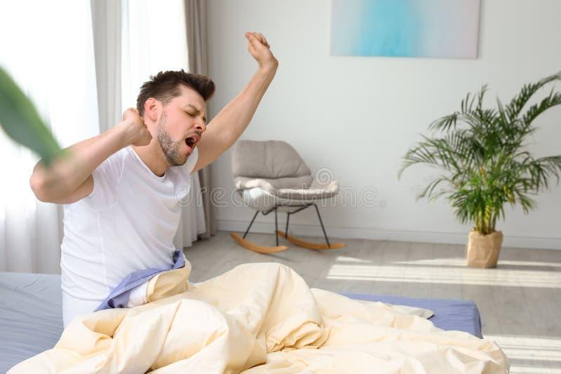 Homem considerável que estica em casa na manhã bedtime imagens de stock royalty free