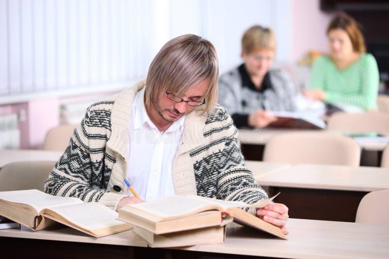 Homem considerável que estuda ao sentar-se na mesa com lote dos livros imagens de stock