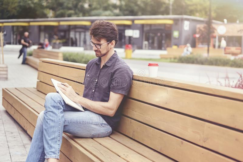 Homem considerável que faz anotações em um livro que senta-se fora Trabalho sozinho vestindo dos vidros do indivíduo Conceito de  fotografia de stock royalty free