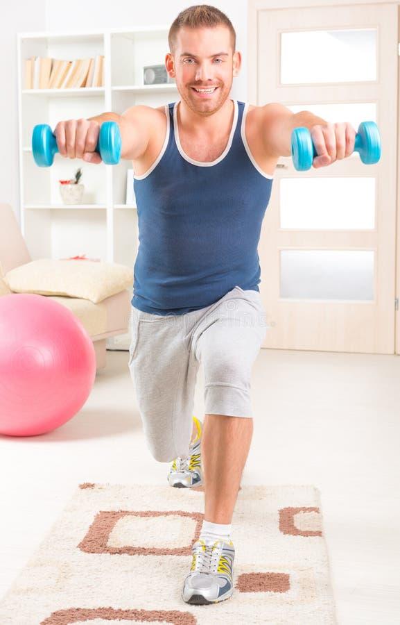 Homem considerável que faz exercícios em casa imagem de stock
