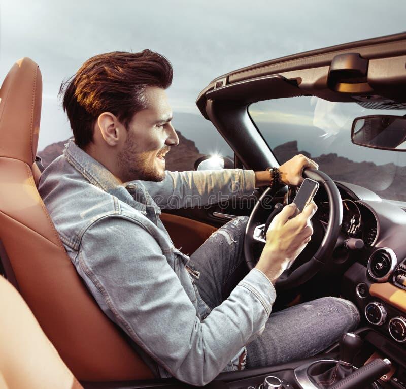 Homem considerável que monta um convertible e que guarda um telefone celular imagem de stock